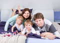 Happy family of a four having fun at home in pajamas in bed Stock Image