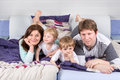 Happy family of a four having fun at home in pajamas in bed Royalty Free Stock Image