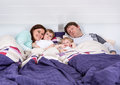 Happy family of a four having fun at home in pajamas in bed Royalty Free Stock Photo