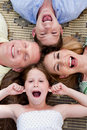 Happy family of four lying on the carpet Royalty Free Stock Photos