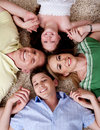 Happy family of four lying on the carpet Stock Photo