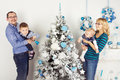 Happy family of four persons decorating christmas tree mother father son daughter Royalty Free Stock Photo