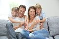 Happy family of four relaxing on sofa Royalty Free Stock Photo