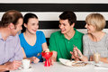 Happy family of four in restaurant cheerful relishing delicious eatables and dessert Royalty Free Stock Image