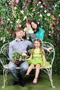 Happy family of four sit on white bench with bunch of flowers and stand behind in garden near verdant hedge Stock Photography
