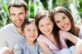 Happy family of four smiling together outdoors Stock Images