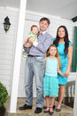 Happy family of four stand on porch of new cottage. Royalty Free Stock Photo
