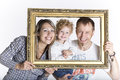 Happy family framed by a picture frame isolated on white Stock Photography