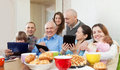 Happy family or friends with electronic devices of three generations group of over tea at home Royalty Free Stock Photo