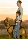 Happy family and german shepherd in sunset father son walking a the Royalty Free Stock Photography