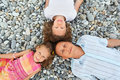 Happy family with girl lying on stony beach Royalty Free Stock Images