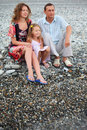 Happy family with girl sitting on beach Stock Photography
