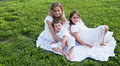Happy family on the grass with white dresses Stock Photos