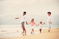 Happy family have fun walking on beach at sunset young Stock Photo