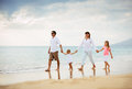 Happy family have fun walking on beach at sunset young Stock Photography