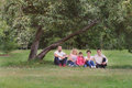 Happy Family have a rest under tree apple Royalty Free Stock Photo