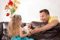 Happy family having fun and giving gifts closeup portrait of adorable caucasian little girl sitting on the sofa from behind Royalty Free Stock Photo