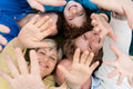 Happy family having fun at outdoors lying on the grass and raising hands Royalty Free Stock Photos