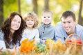 Happy family having picnic in autumn park outdoors against blurred leaves background Stock Images