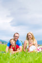 Happy family having picnic in meadow with daughter or kids sitting a summer eating food on Royalty Free Stock Photography