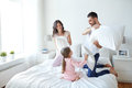 Happy family having pillow fight in bed at home Royalty Free Stock Photo
