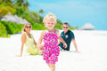 Happy family having tropical vacation running cheerful little girl with her parents Royalty Free Stock Photo