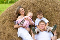 Happy family in haystack together summertime Royalty Free Stock Photo