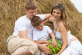 Happy family in haystack w watermelon summertime Royalty Free Stock Images