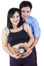 Happy family holding an alarm pregnant women with her husband clock on a white background Stock Photo