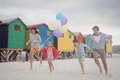 Happy family holding balloons while running at beach Royalty Free Stock Photo