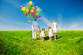 image photo : Happy family holding colorful balloons outdoor. Mom, ded and two