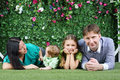 Happy family ie on grass near hedge with flowers of four lie in garden Stock Photos