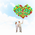 Happy family image of young couple holding bunch of colorful balloons Stock Image