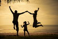 Happy family jumping on the beach on the dawn time Royalty Free Stock Photo
