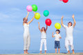 Happy family jumping on the beach at the sunset time. Royalty Free Stock Photo