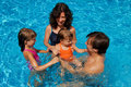 Happy family with kids in swimming pool Stock Photo