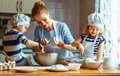 Happy family in kitchen. mother and children preparing dough, ba Royalty Free Stock Photo