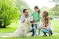 Happy family with labrador retriever dog in park