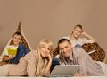 Happy family with laptop is resting together at home Stock Image