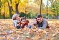 Happy family lies in autumn city park on fallen leaves. Children and parents posing, smiling, playing and having fun. Bright Royalty Free Stock Photo