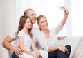 Happy family with little girl making self portrait child photography and home concept digital camera Stock Photography
