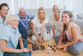 Happy family looking at the camera and playing chess Stock Photos