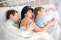 Happy family lying in bed and sleeping funny father mother child hugging concept Stock Image