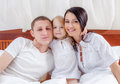 Happy family lying on a bed together in the bedroom Royalty Free Stock Photography
