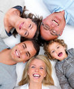Happy family lying in a circle on white floor Stock Image