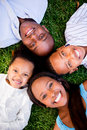 Happy family lying on the grass with their heads together Royalty Free Stock Photos
