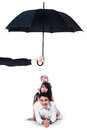 Happy family lying in studio under umbrella Royalty Free Stock Photo