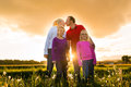 Happy family on meadow at sunset Stock Photos
