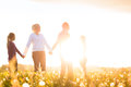 Happy family on meadow at sunset with daughters standing in the summer Stock Image