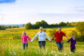Happy family on meadow at sunset with daughters walking in the summer Stock Images